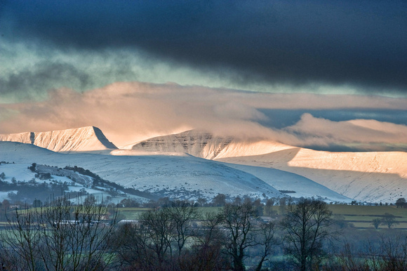 A view of Pen y Fan at sunrise in snow and cloud